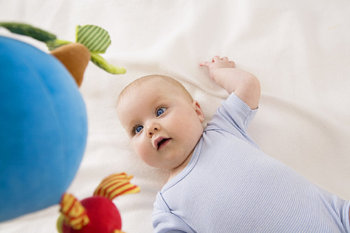 Baby girl looking at toy, smiling - SMOF000527