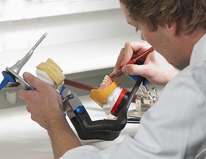 Dentist preparing dentures in dental laboratory - WWF002127