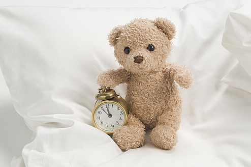Teddy bear with alarm clock on bed - CRF002119