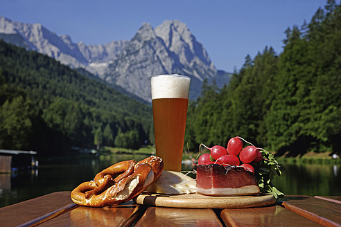 Germany, Upper Bavaria, Bavarian snacks on table, mountain with lake in background - TCF002282