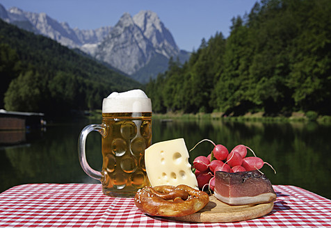Germany, Upper Bavaria, Bavarian snacks on table, mountain with lake in background - TCF002285