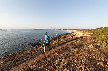 Portugal,Algarve,  Mature man jogging by coast - MIRF000367