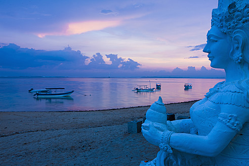 Indonesia, Bali, Sanur, Statue with sea in background at dusk - DSF000299