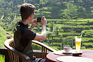 Indonesia, Bali, Tegalalang, Man taking photograph of terraced field - DSF000303