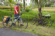 Indonesia, Bali, Tampaksiring, Man with bicycle standing by rural road - DSF000215