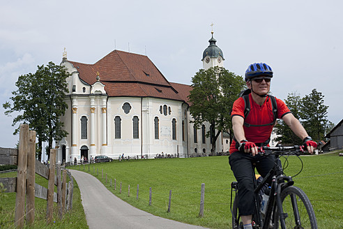 Germany, Bavaria, Mature man riding bicycle with Wieskirche in background - DSF000223