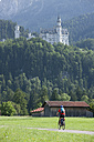 Germany, Bavaria, Mature man riding bicycle, Neuschwanstein Castle in background - DSF000224