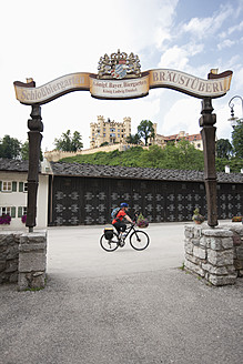 Germany, Bavaria, Mature man cycling to beer garden of Hohenschwangau Castle - DS000282