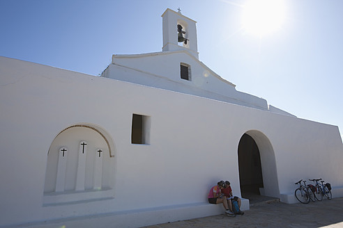 Spain, Ibiza, Mature man and mid adult woman sitting in front of Church - DSF000312