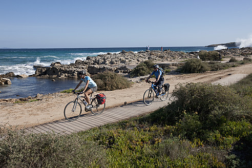 Spain, Formentera, Mature man and mid adult woman riding bicycle - DSF000315
