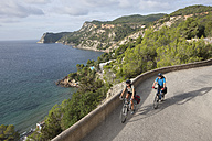 Spain, Ibiza, Mature man and mid adult woman riding bicycle - DSF000322