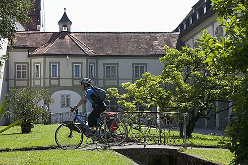 Germany, Bavaria, Man cycling by Abbey Scheyern - DSF000328