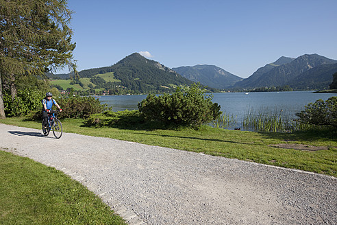 Germany, Bavaria, Man cycling through country road - DSF000334