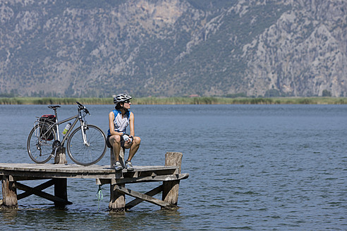 Turkey, Dylan Delta, Mid adult woman sitting on jetty with bicycle - DSF000364