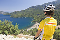 Turkey, Sarsala Bay, Mid adult woman on bicycle looking at bay - DSF000370