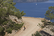 Turkey, Sarsala Bay, Mid adult woman riding bicycle - DSF000373