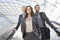 Germany, Leipzig, Business people on escalator, smiling - WESTF018442