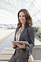 Germany, Leipzig, Businesswoman with digital tablet, smiling - WESTF018451