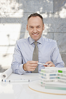 Germany, Leipzig, Businessman with architectural model - WESTF018481