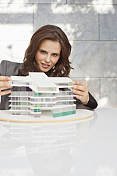 Germany, Leipzig, Businesswoman looking at architectural model - WESTF018502