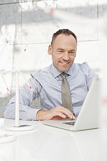 Germany, Leipzig, Businessman using laptop with wind power model - WESTF018511