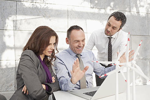 Germany, Leipzig, Business people using laptop and discussing about wind power model - WESTF018523