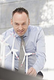 Germany, Leipzig, Businessman with wind power model - WESTF018538