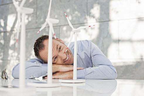 Germany, Leipzig, Businessman with wind power model - WESTF018541