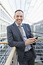 Germany, Leipzig, Businessman with cell phone, smiling, portrait - WESTF018556