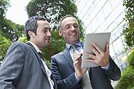 Germany, Leipzig, Business people using digital tablet - WESTF018580