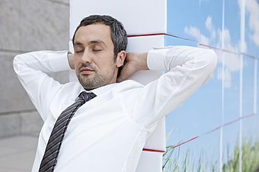 Germany, Leipzig, Businessman resting on cubes - WESTF018589
