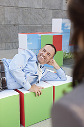 Germany, Leipzig, Business people resting on cubes - WESTF018595