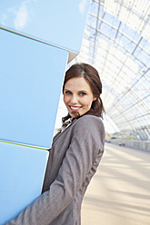 Germany, Leipzig, Businesswoman with cubes, smiling, portrait - WESTF018601