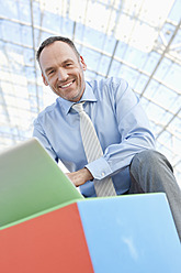Germany, Leipzig, Businessman using laptop with cubes, portrait - WESTF018610