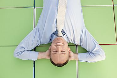 Germany, Leipzig, Businessman resting on cubes, smiling, portrait - WESTF018622