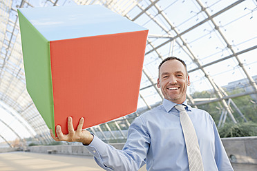 Germany, Leipzig, Businessman holding cube, smiling - WESTF018625
