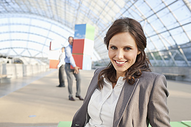Germany, Leipzig, Businesswoman smiling with businessman in background - WESTF018628