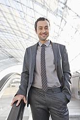 Germany, Leipzig, Businessman on escalator, smiling, portrait - WESTF018634