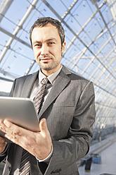 Germany, Leipzig, Businessman using digital tablet on escalator, portrait - WESTF018637