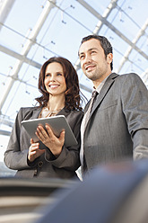 Germany, Leipzig, Business people with digital tablet on escalator - WESTF018643