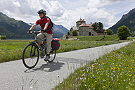 Switzerland, Mature man cycling on country road, Crap da Sass in background - DSF000395