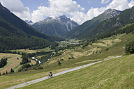 Switzerland, Mature man cycling through country road - DSF000398