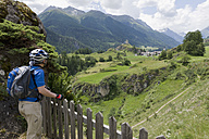 Switzerland, Mature man standing by fence - DSF000440