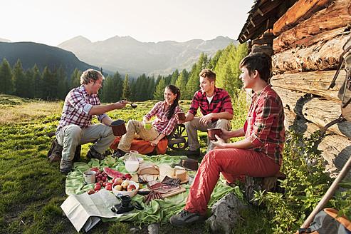 Austria, Salzburg County, Men and women having picnic near alpine hut at sunset - HHF004032
