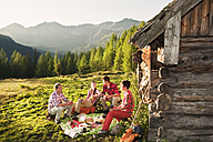Austria, Salzburg County, Men and women having picnic near alpine hut at sunset - HHF004033