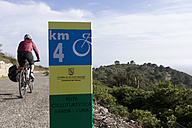 Spain, Mallorca, Woman cycling, road sign in foreground - DSF000406