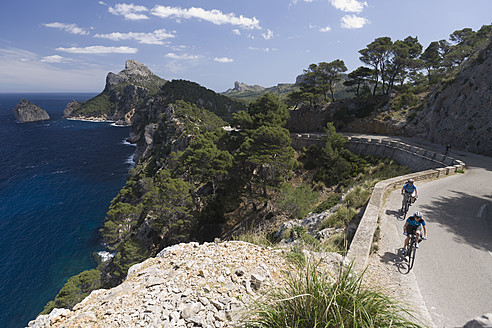 Spain, Mallorca, Man and woman cycling on road at Cap de Formento - DSF000418