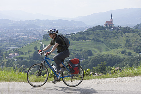 Slovenia, Maribor, Mature man cycling through vineyard - DSF000427
