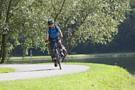Austria, Mature man riding bicycle beside Lake Stubenberg - DSF000436