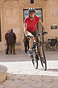 Spain, Menorca, Ciutadella, Woman cycling in street - DSF000499